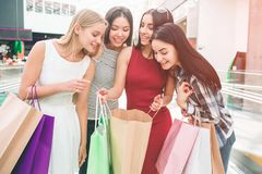 Well-dressed and attractive young women are standing together and looking into one bag. Girl in red dress is holding. Thet bag. She is sharing her happiness stock photography