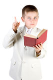 Well-dressed boy read book and lift finger up. Royalty Free Stock Photography