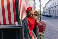 Well-dressed brunette girl standing near cafe with striped exterior with smile. Portrait of cute woman wears trendy