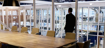 Well dressed businessman looking out window of empty conference room Royalty Free Stock Image