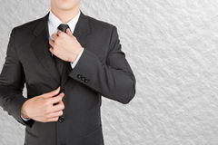Well dressed businessman looklike smart adjusting  his neck tie. On color background : fill text Royalty Free Stock Images