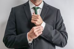 Well dressed businessman adjusting his sleeves. royalty free stock photography