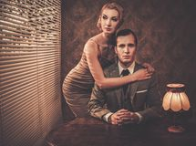 Well-dressed couple in cabinet. Well-dressed retro couple behind table Royalty Free Stock Photo