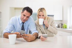 Well dressed couple with coffee cups text messaging in the kitchen Royalty Free Stock Photography