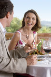 Well-dressed couple dining at table on restaurant balcony Royalty Free Stock Photography