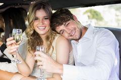 Well dressed couple drinking champagne in a limousine Stock Photos