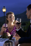 Well-dressed couple drinking red wine on restaurant balcony Stock Photography