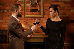 Well-dressed couple with glass of red wine in cozy home interior Stock Image