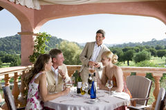 Well-dressed couples drinking wine at table on restaurant balcony Royalty Free Stock Image