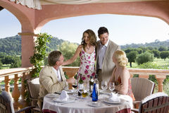 Well-dressed couples drinking wine at table on restaurant balcony.  royalty free stock photos