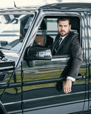 Well-dressed customer choosing new premium car at a dealership showroom.  Stock Photography