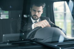 Well-dressed customer choosing new premium car at a dealership showroom.  Royalty Free Stock Photography