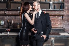 Well dressed famous couple in loft  interior. Couple holding gla. Sses of vine. Studio shot Stock Photo