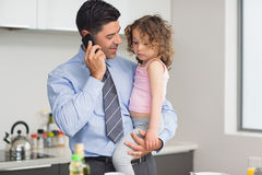 Well dressed father carrying daughter while on call in kitchen Royalty Free Stock Images