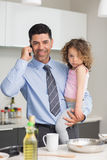 Well dressed father carrying daughter while on call Stock Image