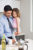 Well dressed father carrying his daughter while preparing food Royalty Free Stock Photography