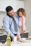 Well dressed father with daughter preparing food while on call Stock Photography