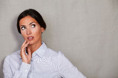 Well-dressed female looking away with hand on chin Stock Images