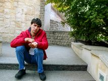 Well dressed handsome young adult man with an outstretched hand imitates begging. Sad look, hand outstretched, the guy is sitting. On the steps in Heydar Aliyev stock photo