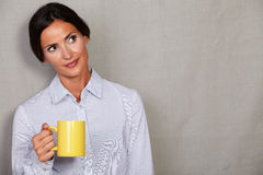 Well-dressed lady standing and holding yellow mug Stock Images