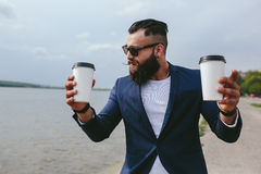 Well-dressed man carries coffee. Stylish bearded man on the background of the lake Royalty Free Stock Image