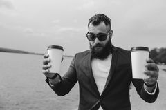 Well-dressed man carries coffee Stock Photo
