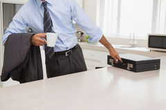 Well dressed man with coffee cup picking briefcase in kitchen Stock Images