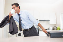 Well dressed man drinking coffee while holding briefcase in kitchen Stock Photo