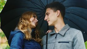 Young beautiful couple standing under an umbrella. It`s raining. The well-dressed man with his wife standing under an umbrella, smiling, laughing stock footage