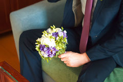 Well-dressed man holding a bouquet of flowers, white roses. Holidays and celebrations. Wedding day. Royalty Free Stock Photography