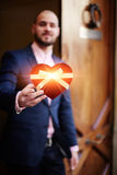 Well-dressed man holding a box of heart-shaped gift on Mother's Day Stock Photo