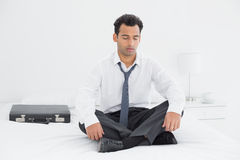 Well dressed man sitting with eyes closed on bed at home Royalty Free Stock Images