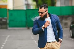 Well-dressed man smoking electronic cigarette. Man with a beard smokes electronic cigarette Royalty Free Stock Images