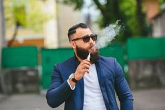 Well-dressed man smoking electronic cigarette. Stylish bearded man walks through the city Royalty Free Stock Photos