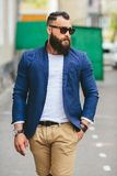 Well-dressed man smoking electronic cigarette. Stylish bearded man walks through the city Royalty Free Stock Images