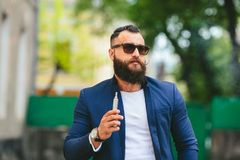 Well-dressed man smoking electronic cigarette Royalty Free Stock Image