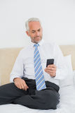 Well dressed man text messaging in bed Royalty Free Stock Photo