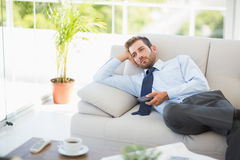 Well dressed man watching tv in the living room Stock Image