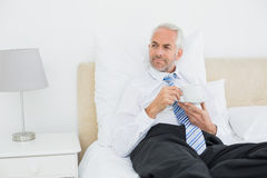 Well dressed mature man with a cup of tea in bed Stock Images