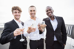 Well dressed men drinking champagne next to a limousine Stock Photos