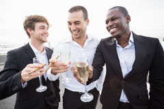 Well dressed men drinking champagne next to a limousine Royalty Free Stock Image