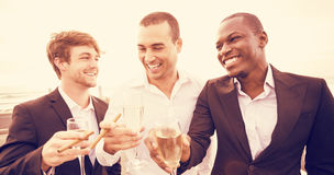 Well dressed men drinking champagne next to limousine Stock Image