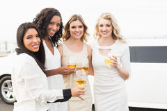 Well dressed men drinking wine next to a limousine Royalty Free Stock Photos