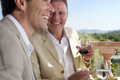 Well-dressed men drinking wine on restaurant balcony Stock Photo