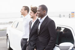Well dressed men posing leaning on a limousine Stock Photography