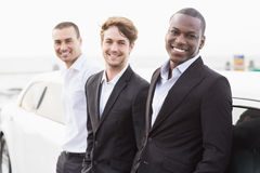 Well dressed men posing leaning on a limousine Royalty Free Stock Photo
