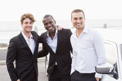Well dressed men posing next to a limousine Royalty Free Stock Photography