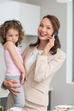 Well dressed mother carrying daughter while on call in kitchen Royalty Free Stock Photo