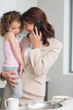 Well dressed mother carrying daughter while on call in kitchen Royalty Free Stock Photos