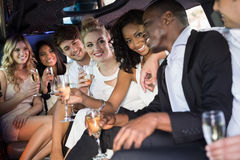 Well dressed people drinking champagne in a limousine Royalty Free Stock Images